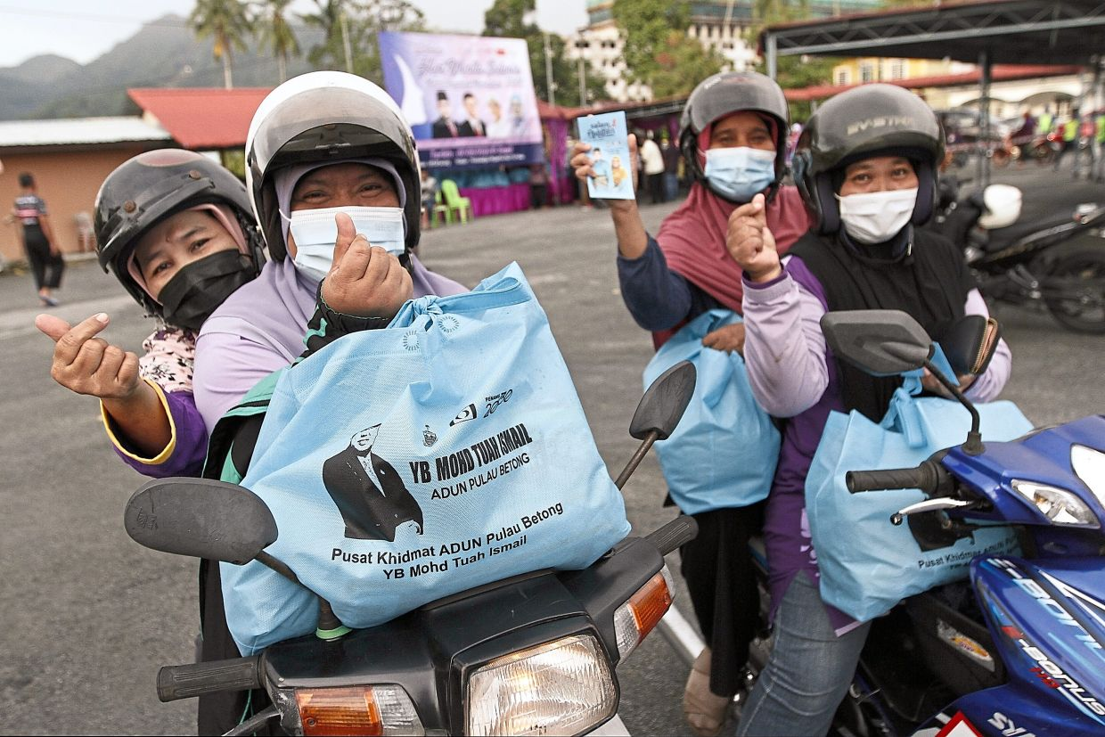 Residents giving the thumbs up after receiving hampers in  conjunction with International Women's Day celebration near Titi Teras mosque in Balik Pulau, Penang.