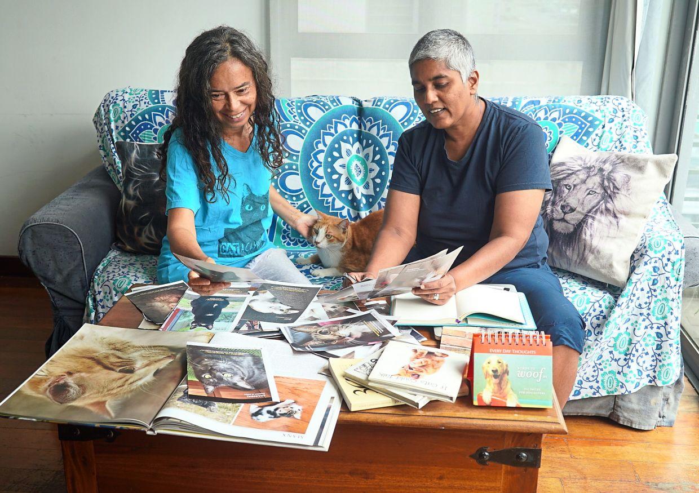 Catherine Leyow (left) and Sherrina Krishnan-Leyow looking through the numerous cat pictures for the desktop book project. Photo: Sherrina Krishnan-Leyow