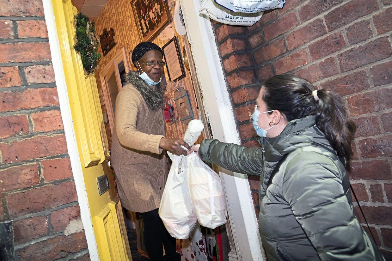 Volunteer Maria Martinez (right) handing bags of West Indian meals to Bridgette Toussaint.