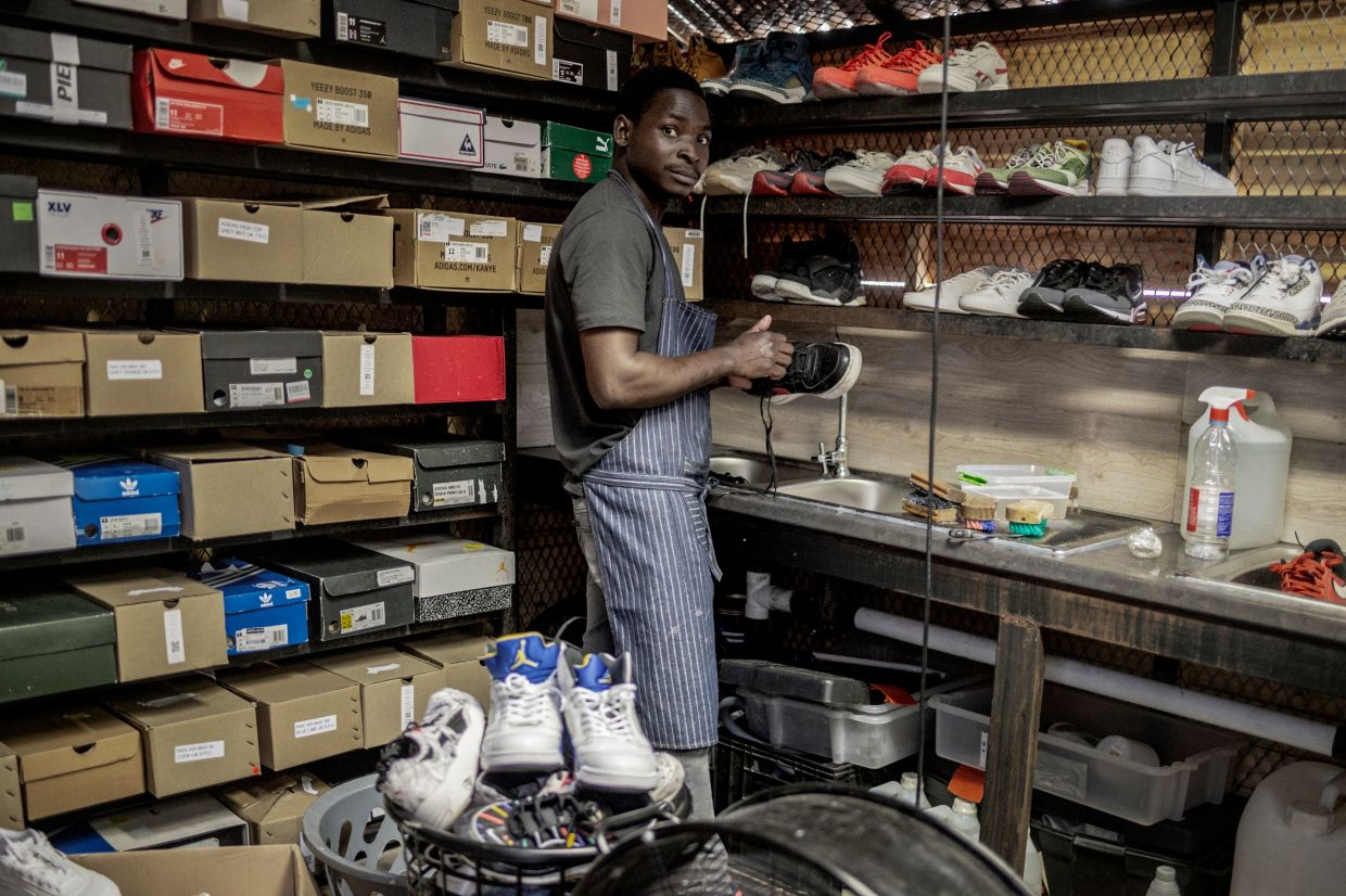 A worker stands in a vintage sneakers reseller shop in Johannesburg. Photo: AFP