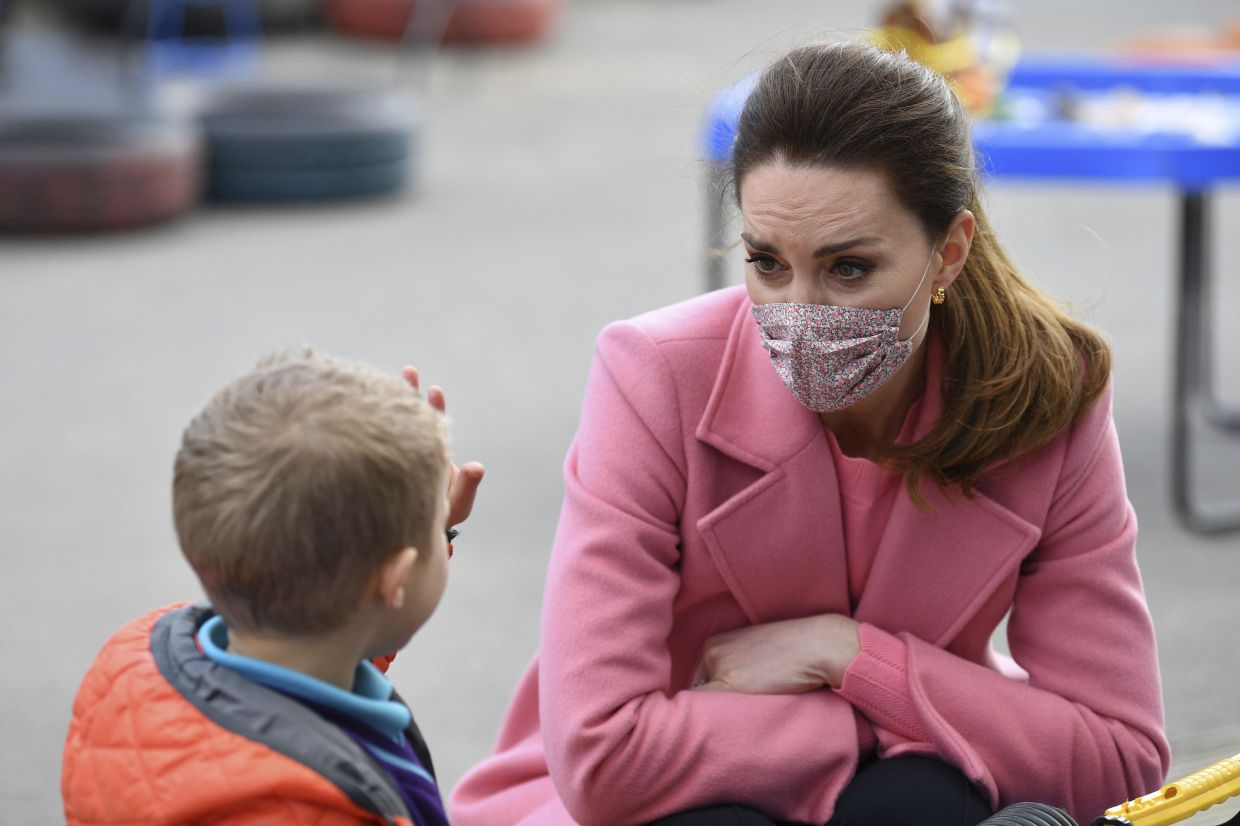 Britain's Kate, Duchess of Cambridge watches as a child holds up five fingers to indicate his age during a visit with Prince William to School21, a school in east London. Photo: AP