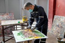 Artist fights waste by using recycled trash to create paintings