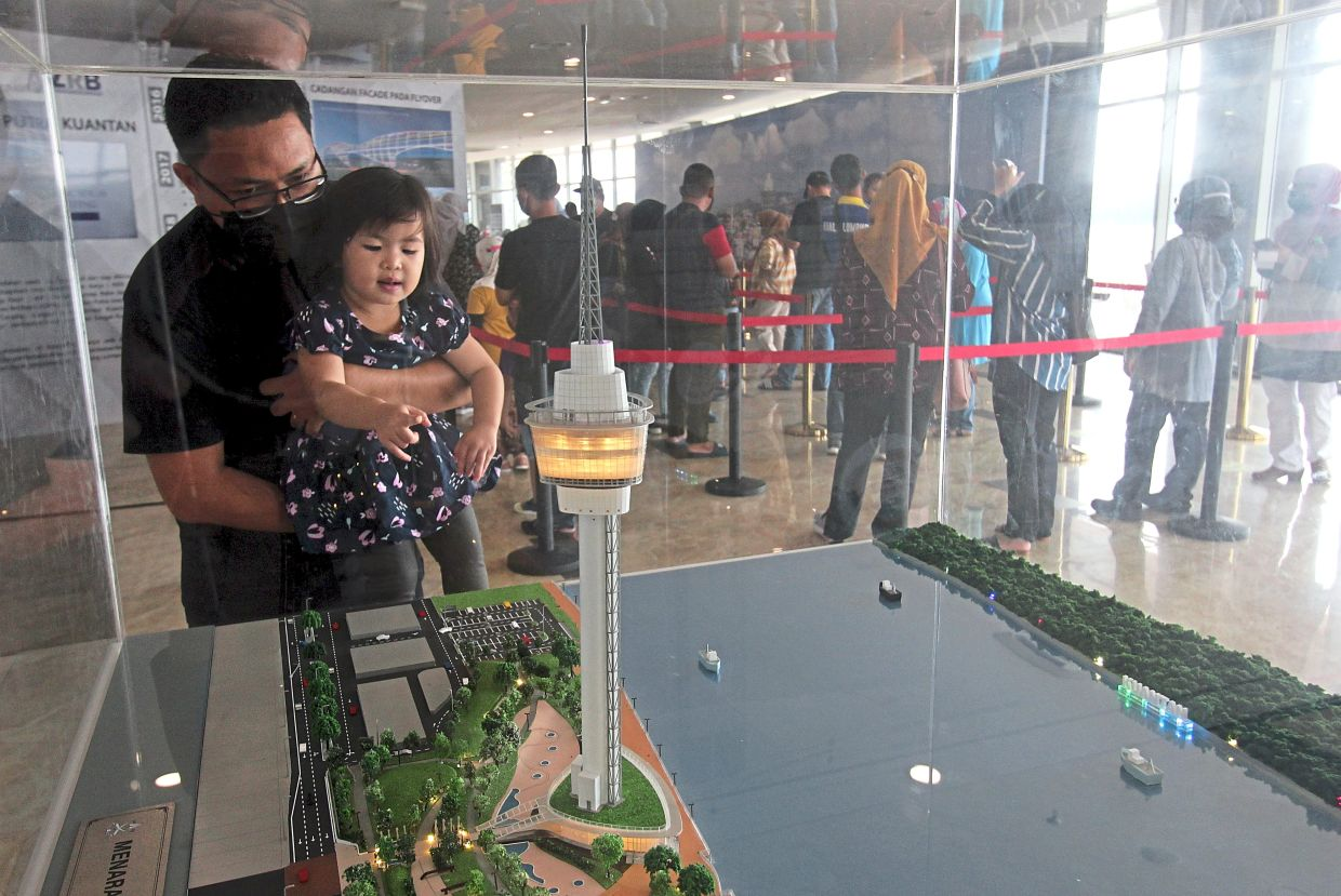 Mohd Nasuha Mohd Zaini, 30, carrying his daughter Nafisah to have a better view of the model of the Kuantan 188 Tower, while waiting for their turn to see the city view from the tower. — Bernama