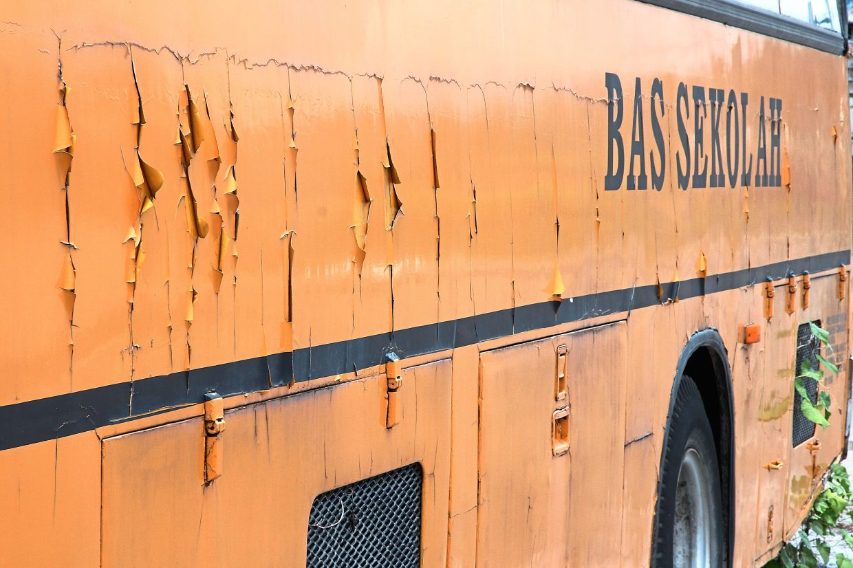 Paint peeling off a school bus parked by the roadside near a bus depot after months of not being used.