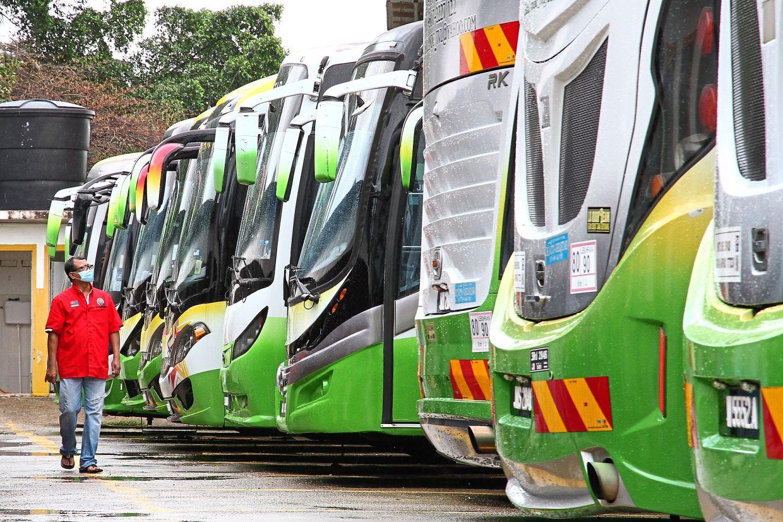 Bus operator Abdullah Abd Ghani, 50, walking past dozens of buses parked at a depot.