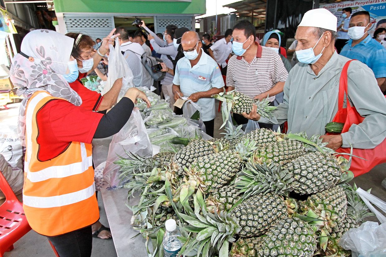 Visitors buying fresh fruits and vegetables at the event.