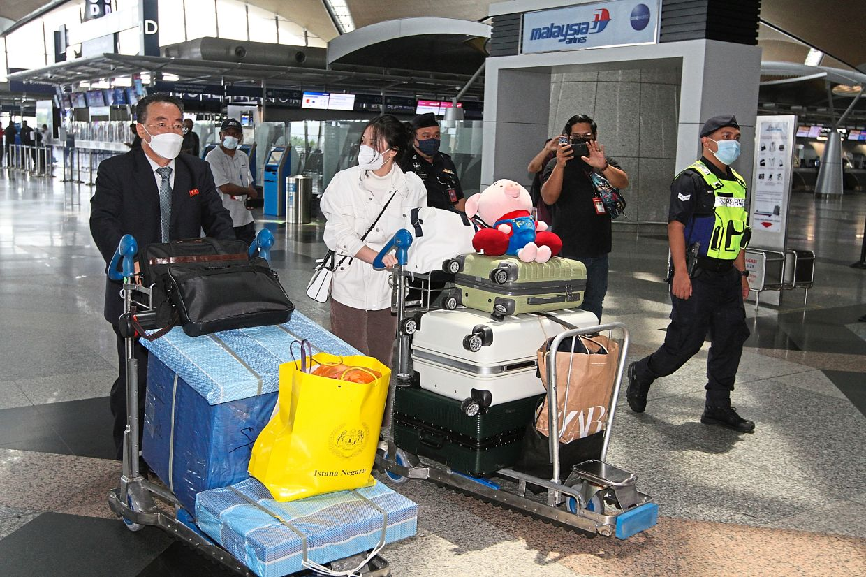 Hasty exit: (Below) Diplomats and staff loading up a bus and leaving for KLIA and (top) Kim Yu-song arriving at KLIA before boarding a Shanghai commercial plane. — LOW BOON TAT/The Star