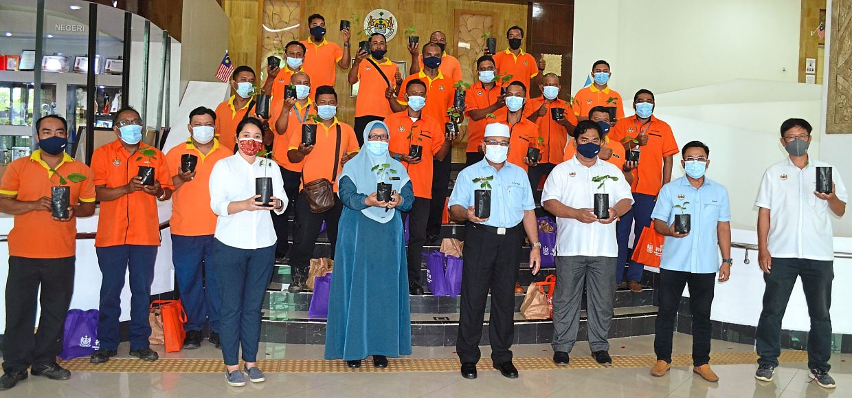 Rozali (with songkok) and Wira Oren members with the seedlings they received at the MBSP headquarters in Bukit Mertajam. Joining them (front row, from left) are Teh, Rosnani, Muhamad Suzuki, Anuar and Tan.