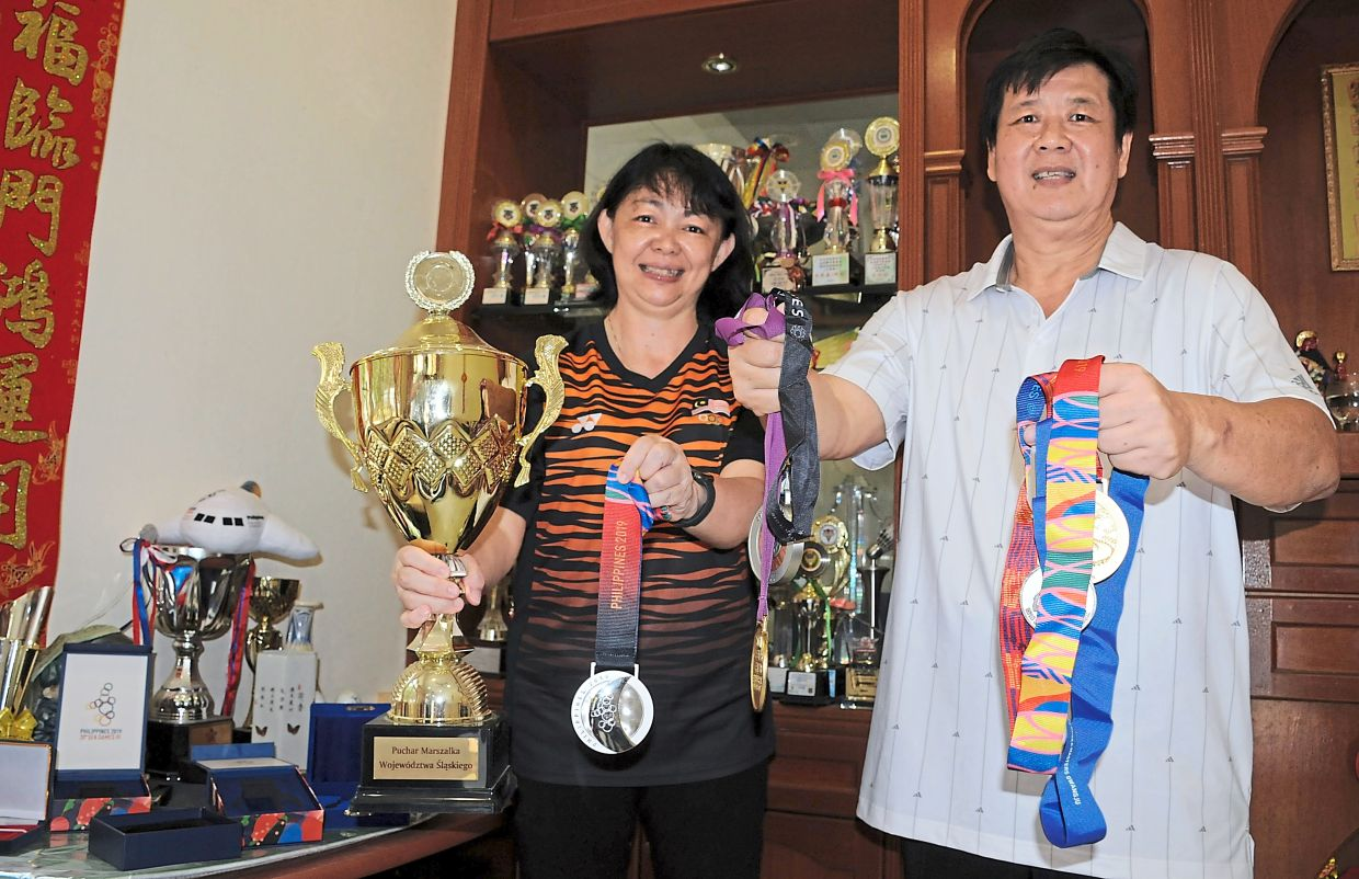 Proud parents: Leow and Lee showing some of Zii Jia's medals at their home in Bandar Darulaman, Jitra, Kedah. — GC TAN/The Star