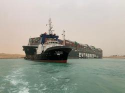 Tugs work to free giant container ship stranded in Suez Canal