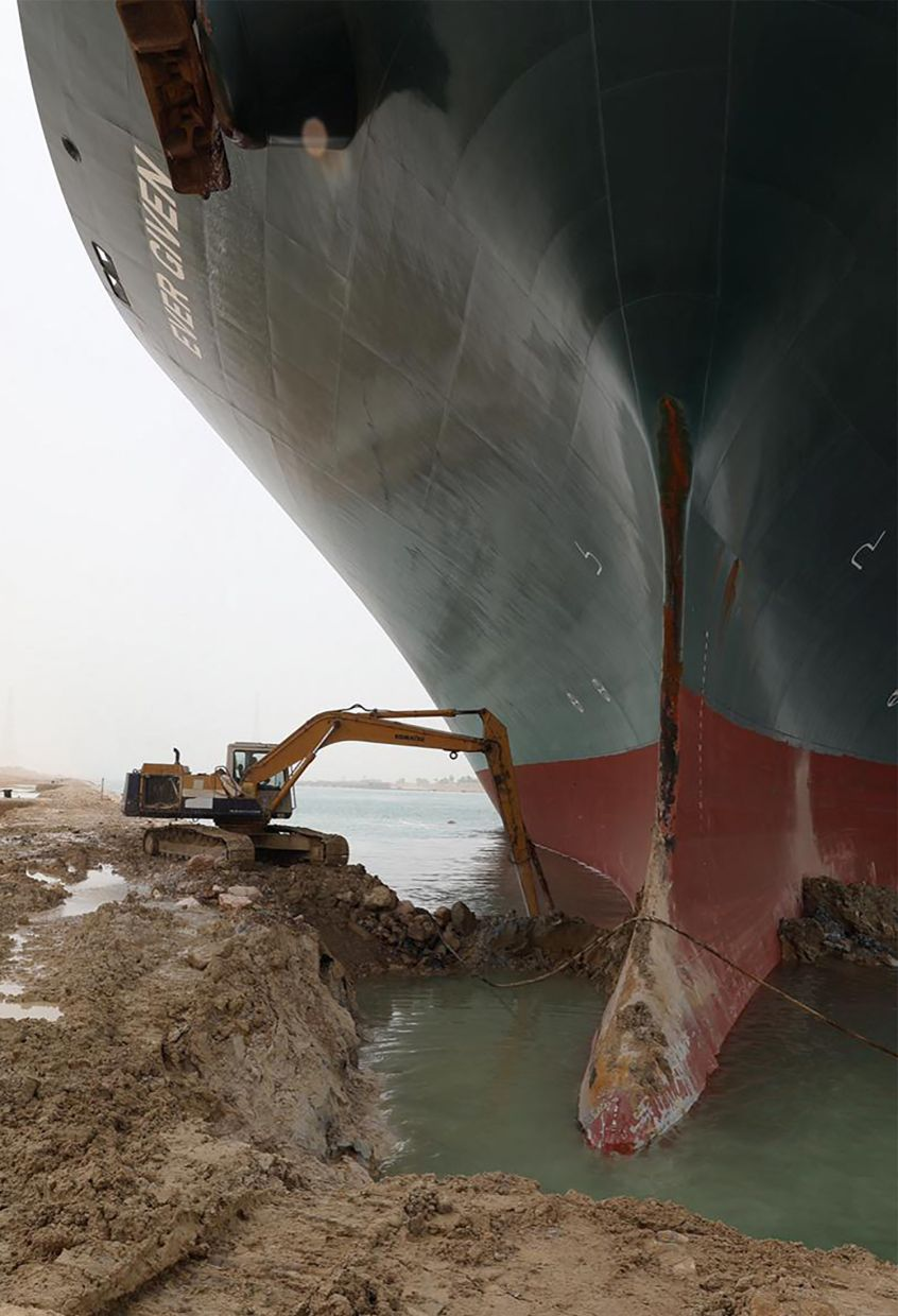 From the shore, excavators are also working around the vessel. Photo: AFP
