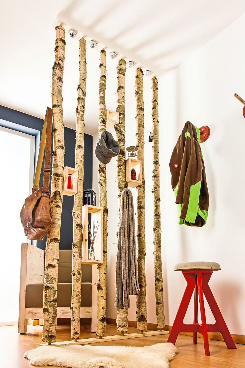 A few birch logs placed a little distance apart can form a room divider – and can also serve as a coat rack.
