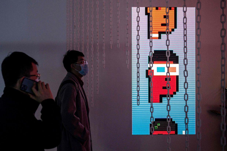 Gallery visitors look at CryptoPunks' digital characters. Photo: AFP