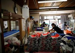 Olympic torch relay ignites business recovery hope of Fukushima flag maker