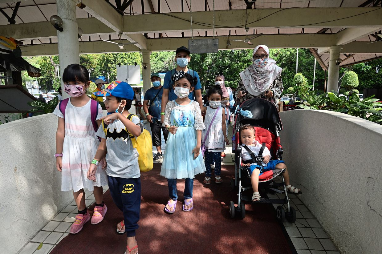 Mohd Rashid Murad and his wife Saidah Asilah Abdul Shukor with their children getting ready to enter the Kuala Lumpur Bird Park on a weekend visit.
