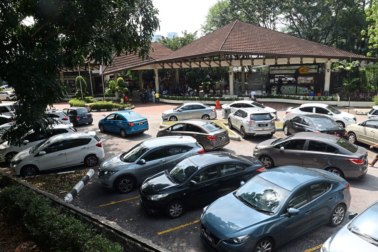A long queue of cars looking for parking at the Kuala Lumpur Bird Park on a weekend.
