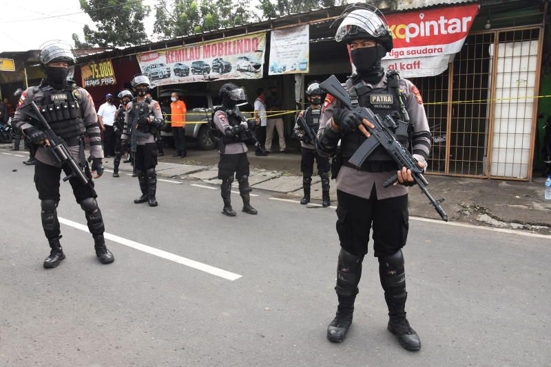 Armed police officers stand guard outside a house of suspected militants during a raid in Jakarta, Indonesia, on Monday, March 29, 2021. - Antara Foto via Reuters