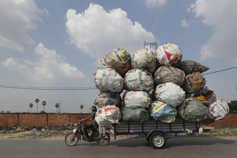 A biker carrying huge bags of recyclables travels on a street outside Phnom Penh, Cambodia. - AP