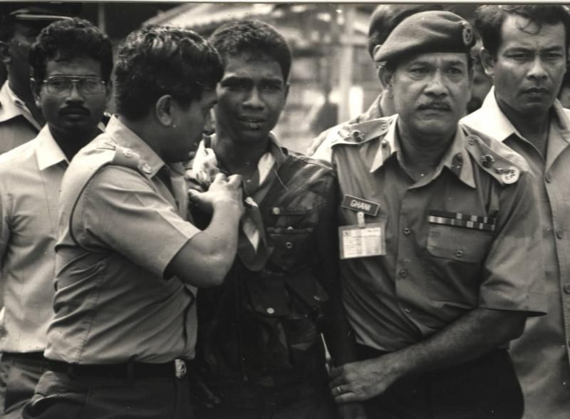 Surrender: Prebet Adam (centre) being led away after his surrender. Scanned Pix : Staric Date : 09.10.1987