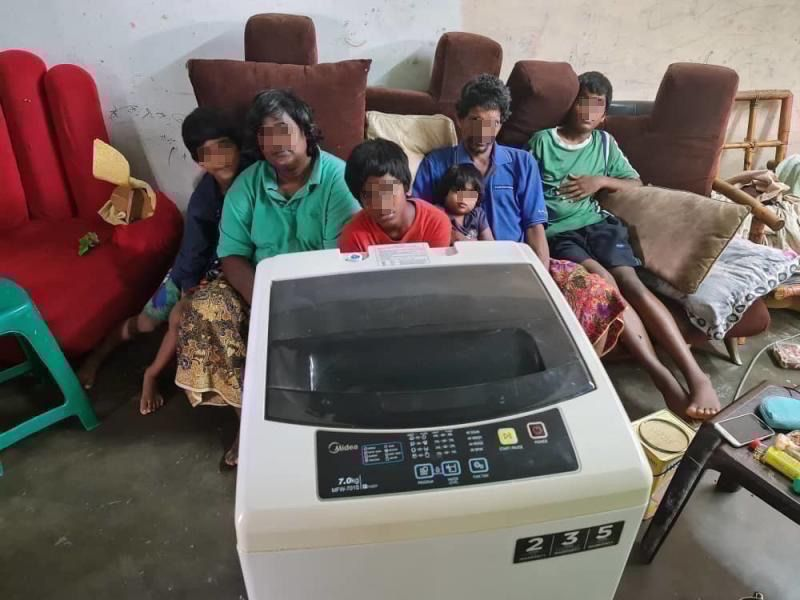 A family in PPR Bukit Jalil receiving a washing machine through the project.