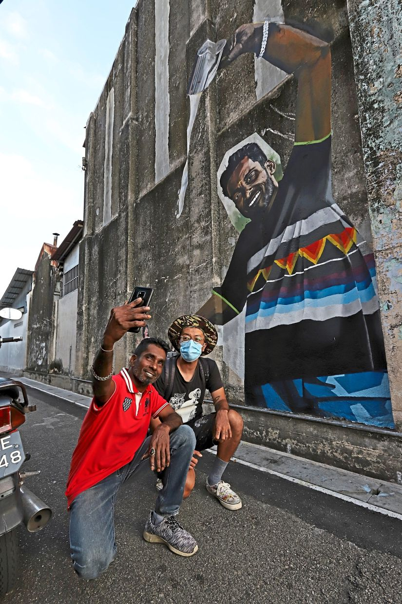 Pulled milk seller Kathiravelu (left) taking some photos with artist Khow Zew Wey who painted the 'Susu Tarik' mural featuring the former.