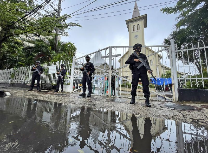 Armed police officers stand guard at the gate of the Sacred Heart of Jesus Cathedral which was attacked by suicide bomb on March 28, ahead of Mass on Good Friday, April 2, 2021, in Makassar, South Sulawesi, Indonesia. On Sunday, a recently married couple with suspected militant links used pressure cooker bombs to blow themselves up outside the cathedral in the capital of South Sulawesi province. - AP