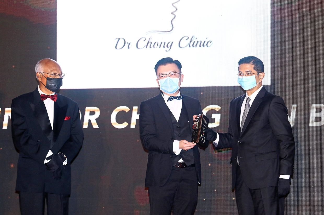 Strong motivation: Chong (middle), receiving his award from Azmin (right) as Mohd Aminuddin looks on, says his team is motivated to do better.