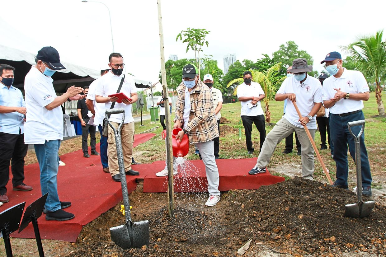 Annuar (centre) watering a Tecoma tree at the Metropolitan Batu Park when launching the programme to plant one million trees, while Mahadi (left) looks on. — LOW LAY PHON/The Star