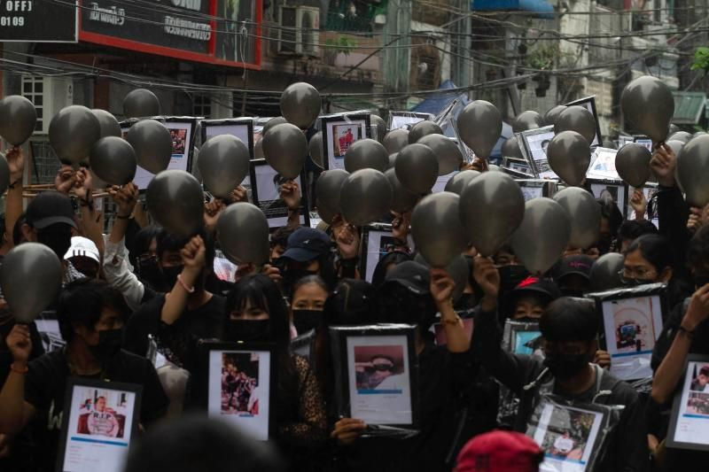 This photo taken and received from an anonymous source via Facebook on April 5, 2021 shows protesters holding up portraits of people who have died while taking part in the demonstrations against the military coup, at a rally in Yangon. - AFP
