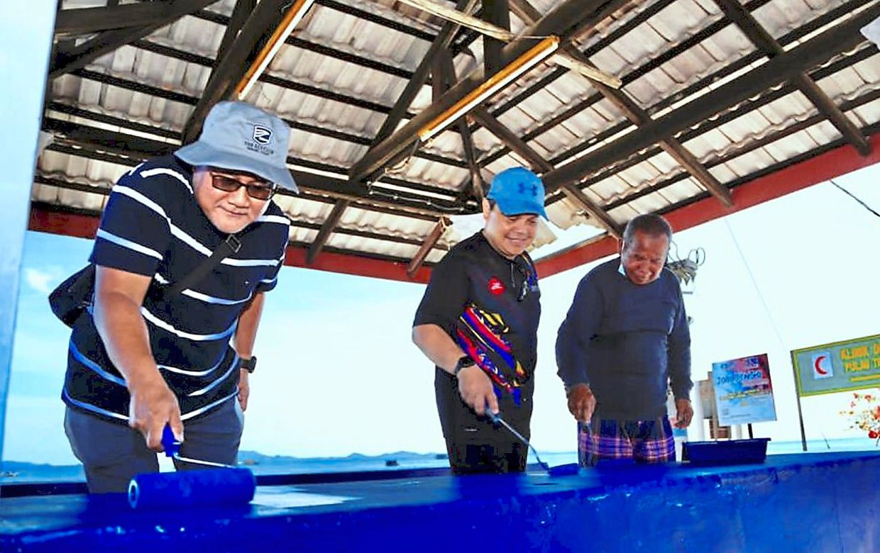 (From left) Mohd Noorazam, Sports Johor Sdn Bhd chief executive officer On Jabbar and Pulau Tinggi former village chief Razali Ali painting  a shed near the jetty, during the event at Pulau Tinggi, Mersing, Johor.