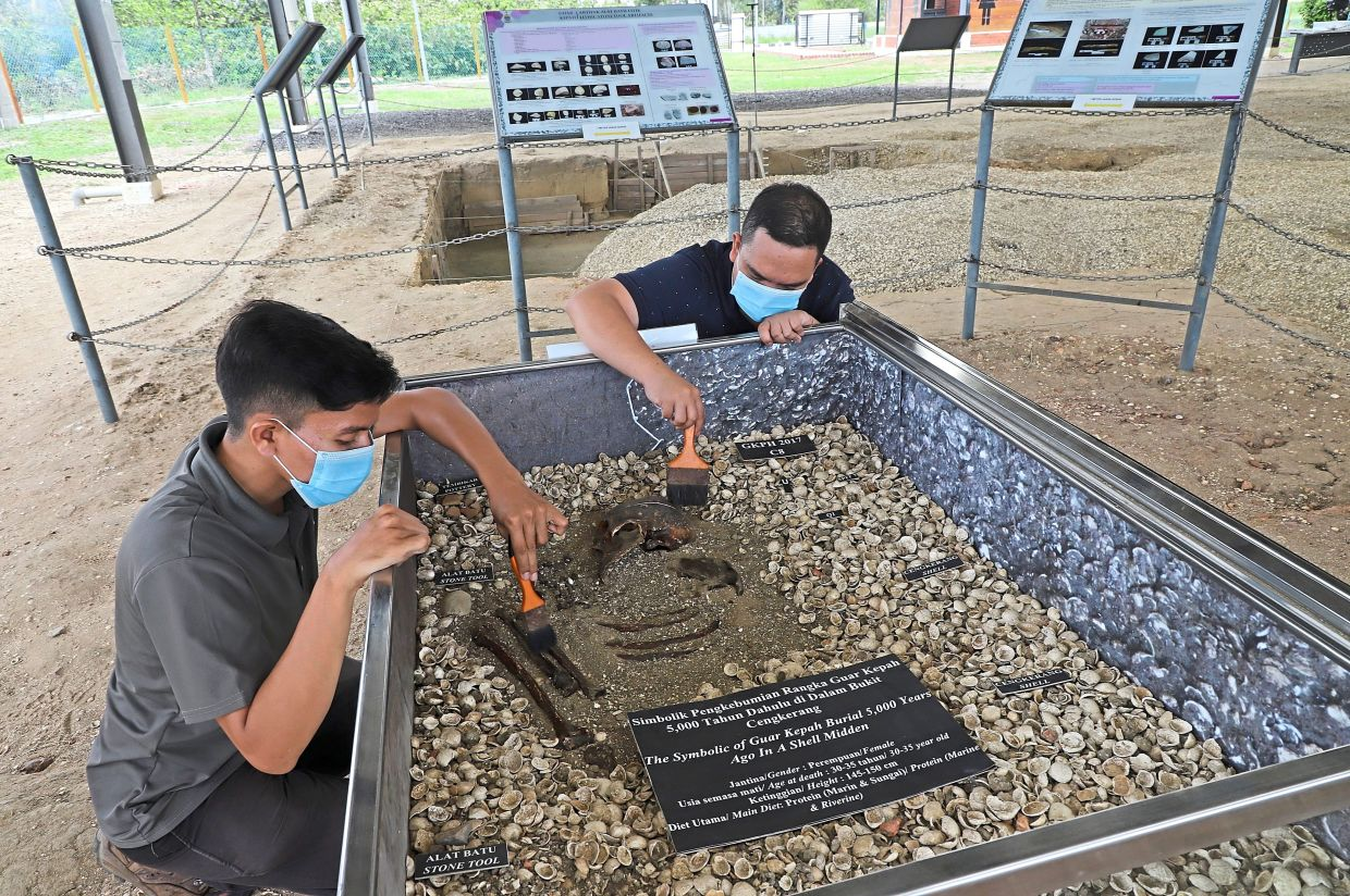 Muhamad Hafizuddin (left) with his colleague Zul Fahmi Abdul Halim dusting a replica of Penang Woman at the Guar Kepah Archaeological Site in Kepala Batas. – Photos and video: LIM BENG TATT/The Star