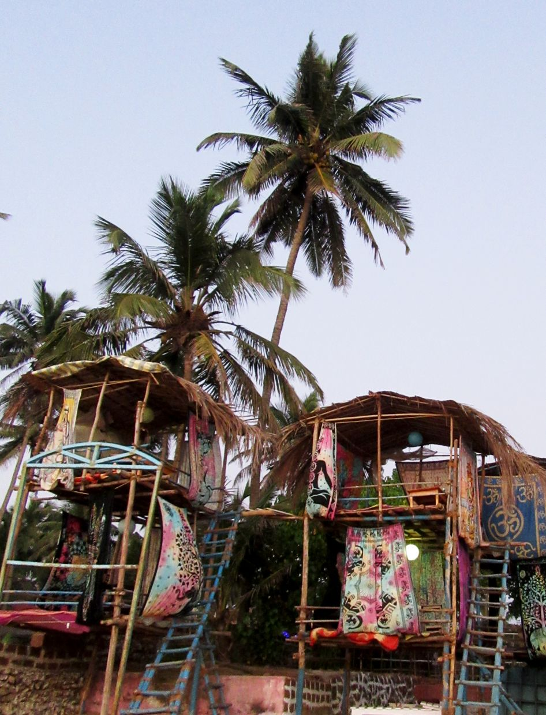 Pavilions under palm trees on Anjuna Beach, a tourist area.