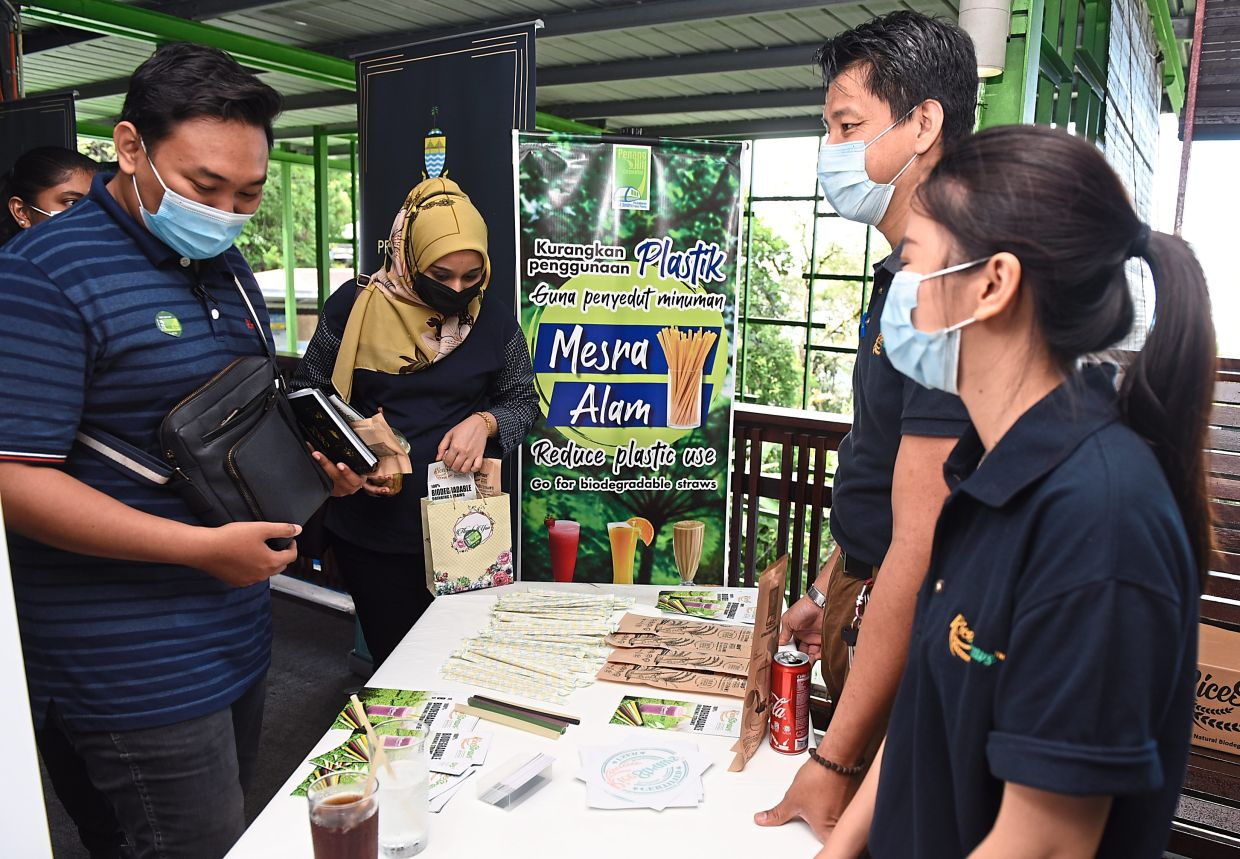 Customers looking at the display promoting the use of rice straws at the food court on Penang Hill.