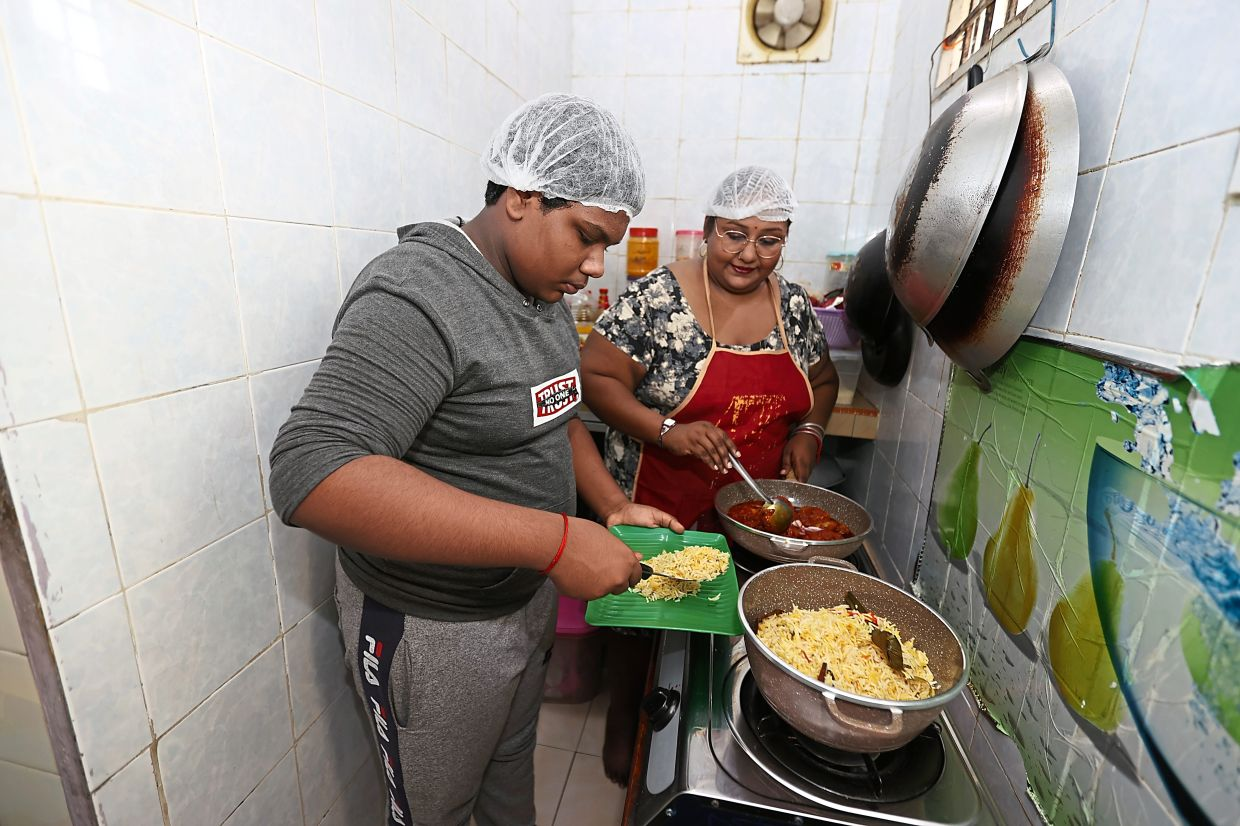 Navamalar (right) cooking in her home-based kitchen, and assisted by her son, Thurgeswaran. Photo: The Star/Glenn Guan