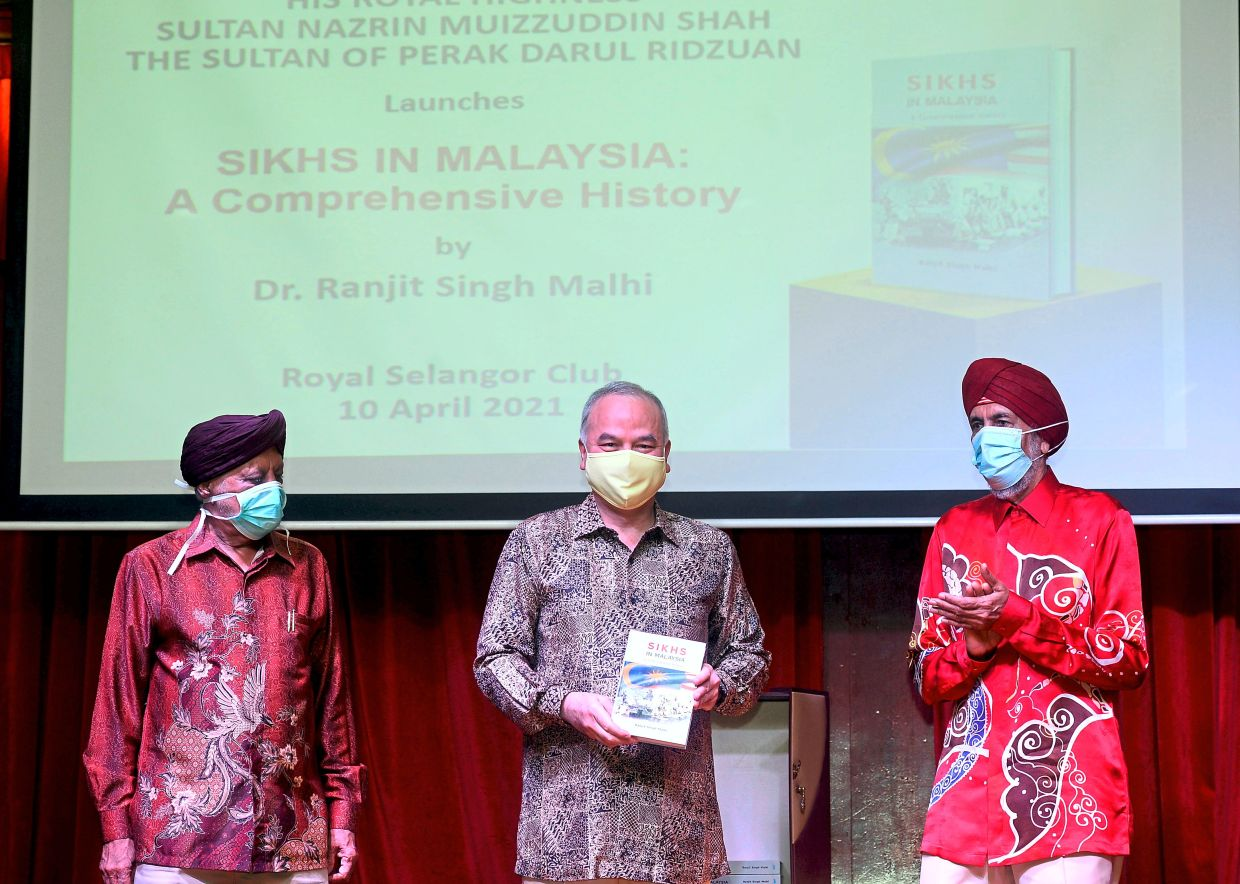 Royal support: Sultan Nazrin holding a copy of 'Sikh In Malaysia' during its launch at the Royal Selangor Club in Kuala Lumpur. He is joined by Ranjit (left) and Ranjit's brother Gurdev Singh Malhi.