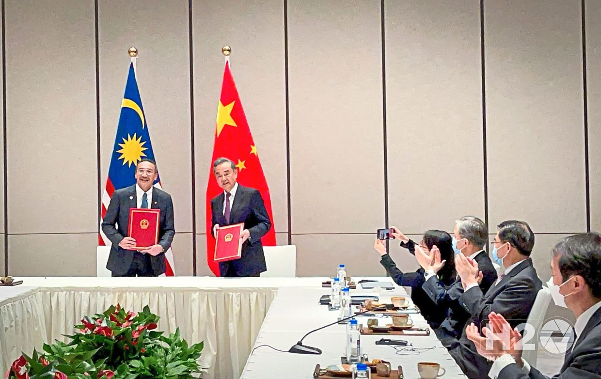 Hishammuddin (left) and his Chinese counterpart Wang at the signing of the historic MOU on the Establishment of a High-Level Committee to Promote Co-operation in the Post Covid-19 Era.