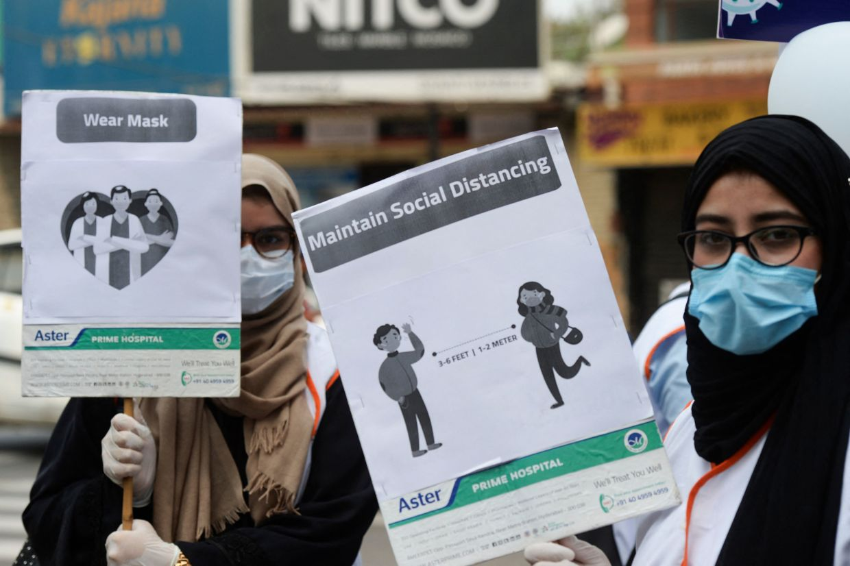 Medical staff urging people to follow Covid-19 coronavirus guidelines in Hyderabad, India, on World Health Day. — AFP