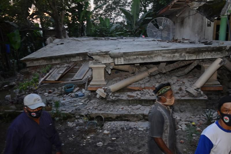 Villagers walking past a collapsed house at Sidorenggo village, in Malang, East Java on April 10, 2021 after a 6.0 magnitude earthquake struck off the coast of Indonesia's Java island. - AFP