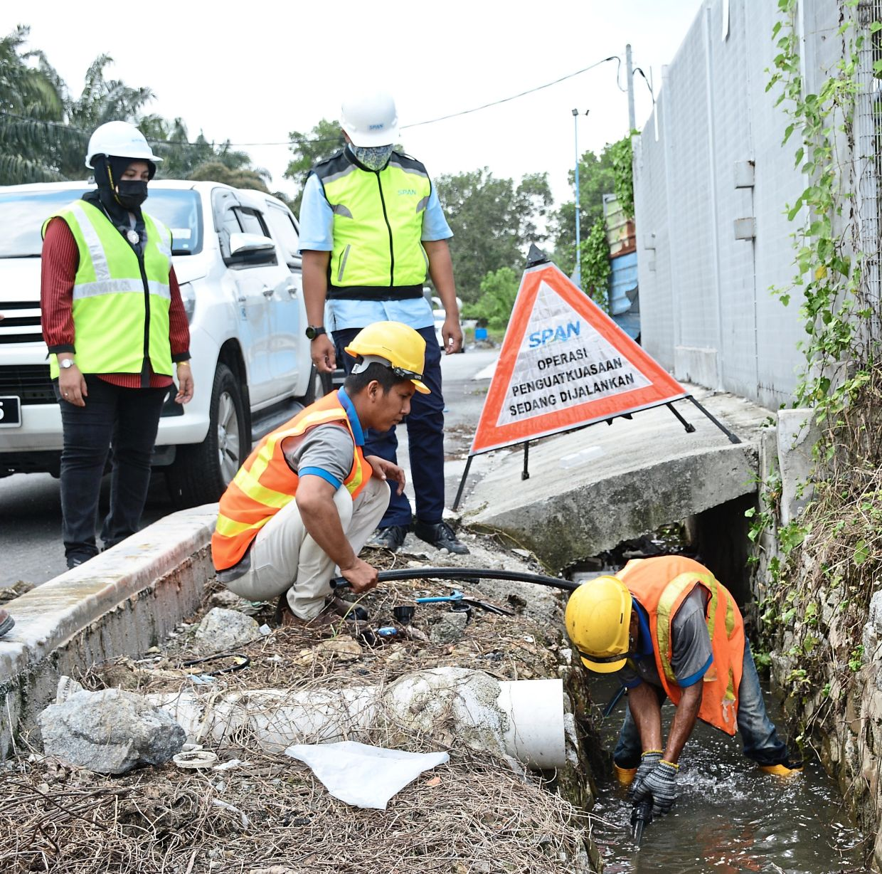 Finding the leak:  SPAN workers disconnecting an illegal pipe during an operation at a scrapyard  in Teluk Panglima Garang, Banting. — LOW BOON TAT/The Star