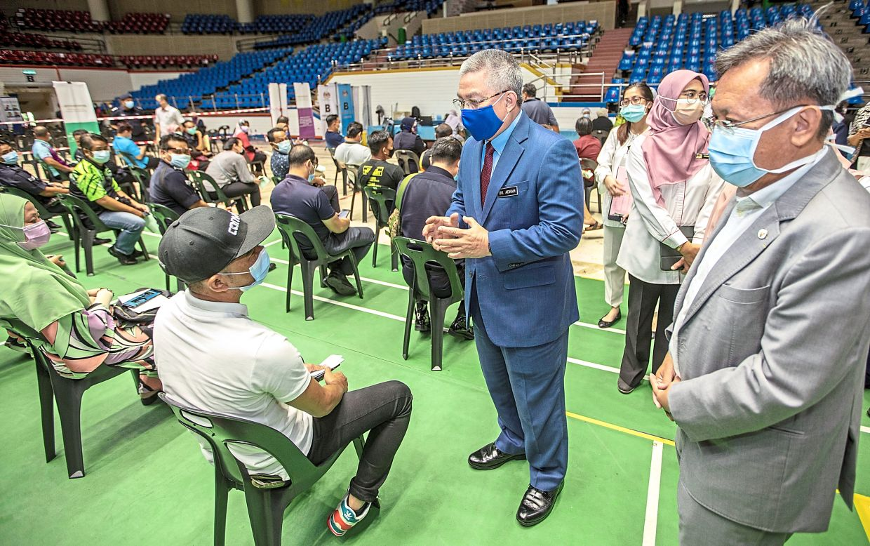 Ongoing effort: Dr Adham (in blue suit) talking to frontliners while observing the National Covid-19 Vaccination Programme at the Indoor Stadium in Kuching. — ZULAZHAR SHEBLEE/The Star