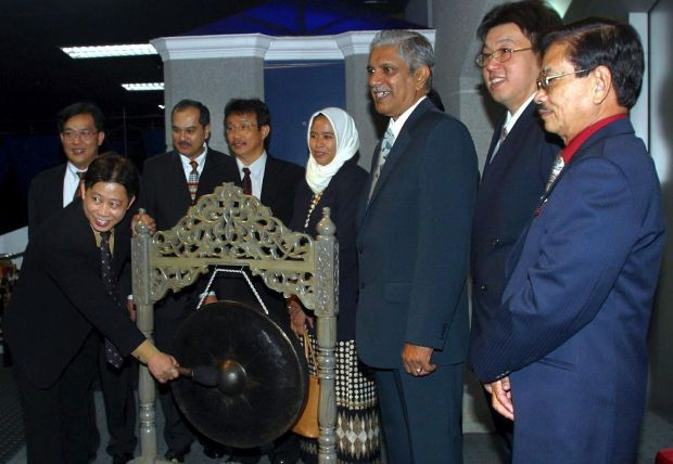 Group managing director and founder of Luster Industries Lim See Chea striking the gong to mark the company\'s listing on the KLSE main board in Kuala Lumpur on September 11 2003. With him are other company directors. - The Star file pic