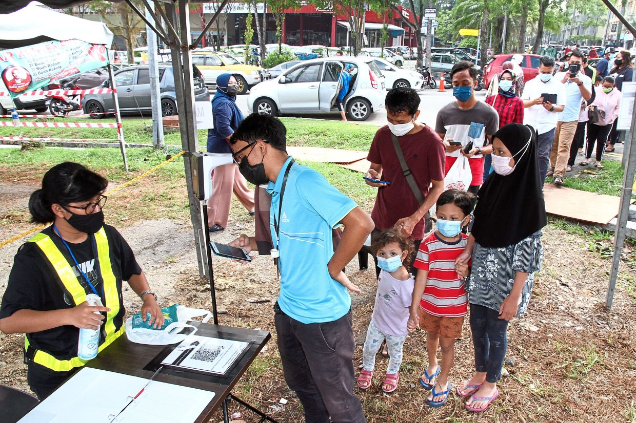 People observing the SOP by checking their temperature before entering the Ramadan bazaar at Southern City in Johor Baru. — Photos: THOMAS YONG/The Star