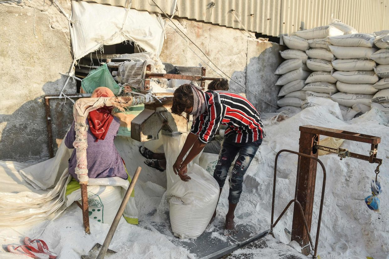 Labourers working at a salt farm, where the work is both tedious and taxing.