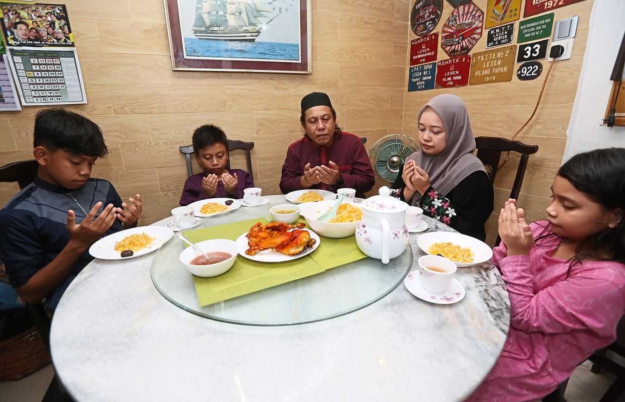 Prayers before breaking fast during iftar. Photo: The Star/Izzrafiq Alias