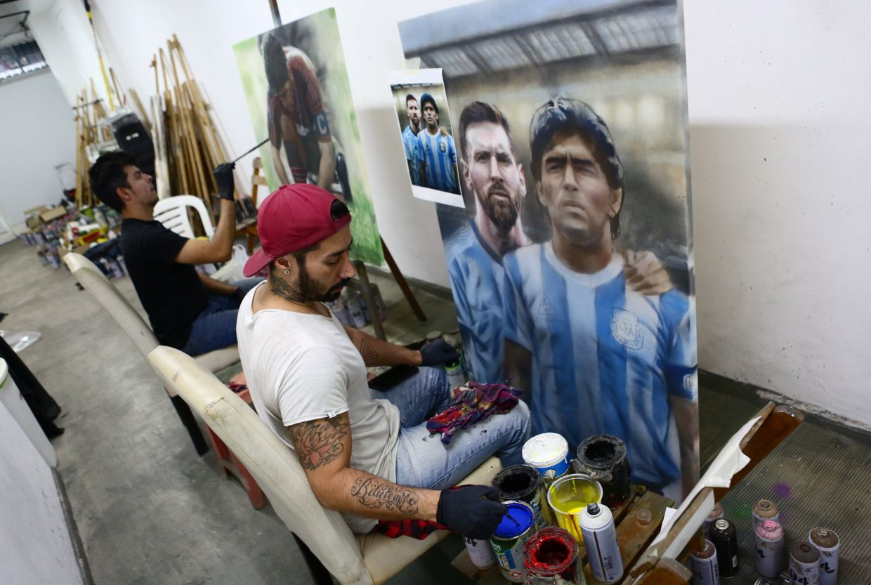Bagnasco finishes a painting of Maradona, and Lionel Messi, next to his assistant Dreier Salamanca at their workshop in Buenos Aires. Photo: Reuters