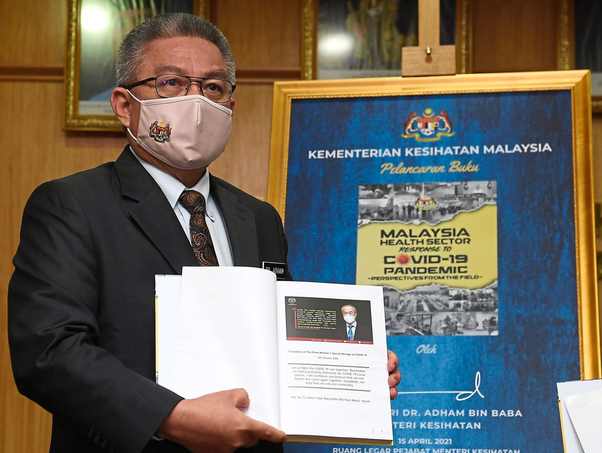Read all about it: Dr Adham holding the 'Malaysia Health Sector Response to Covid-19: Perspectives From The Field' during its launch in Putrajaya. — Bernama