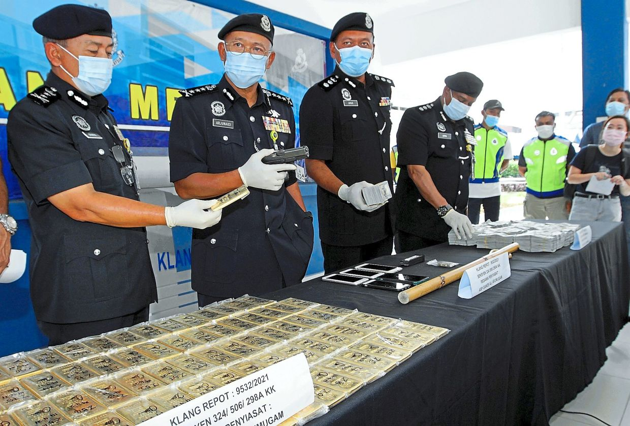Large haul: Comm Arjunaidi (second from left) showing the pistol and gold bars as well as other seized items during a press conference at South Klang police headquarters in Klang. — KK SHAM/The Star