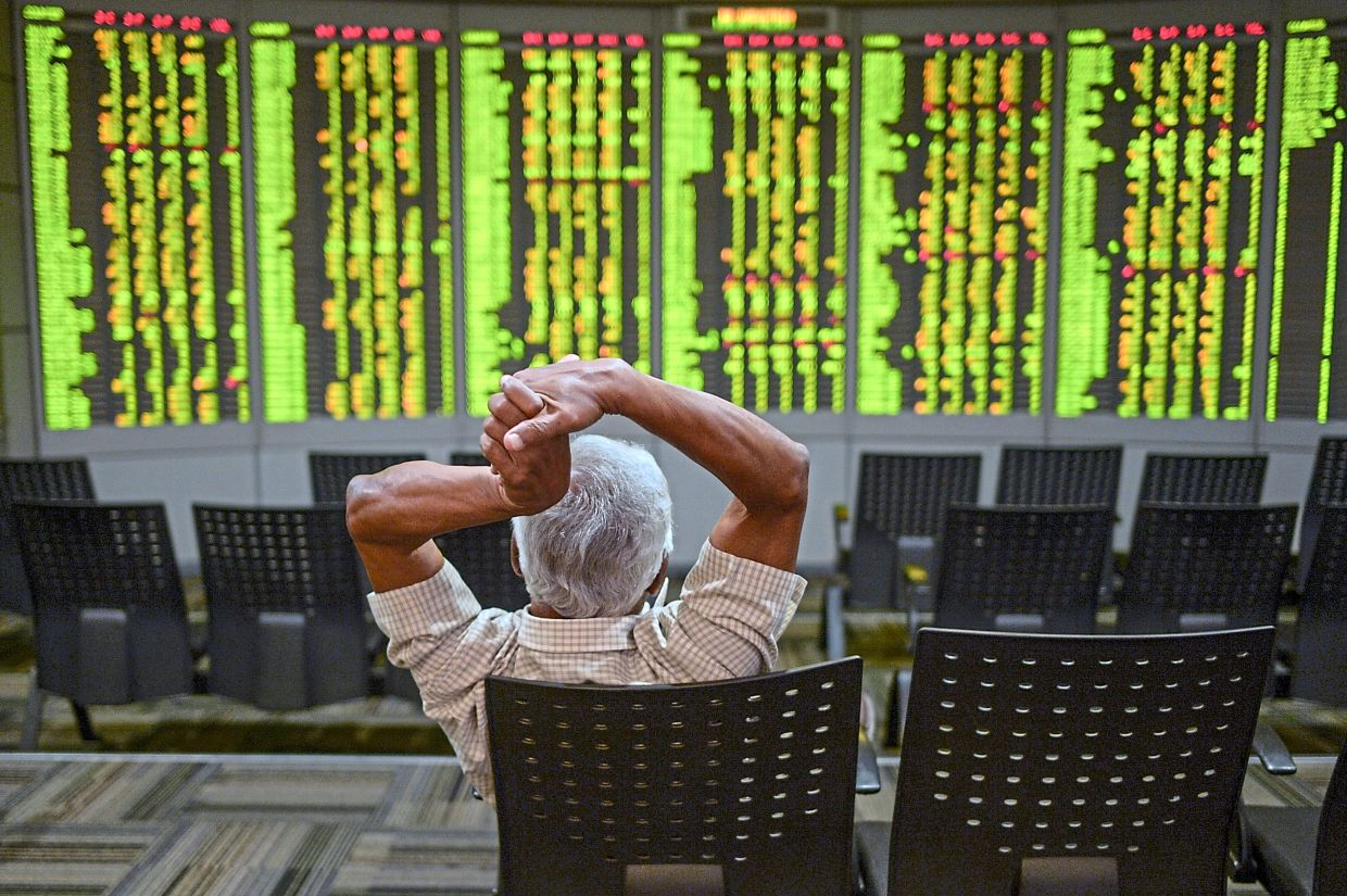 Rallying: A man monitoring stock movements at a private trading firm in Kuala Lumpur. Improving earnings prospects and rising participation from retail investors in the equity market are the main drivers of the uptrend in the FBM Small Cap Index. ─ AFP