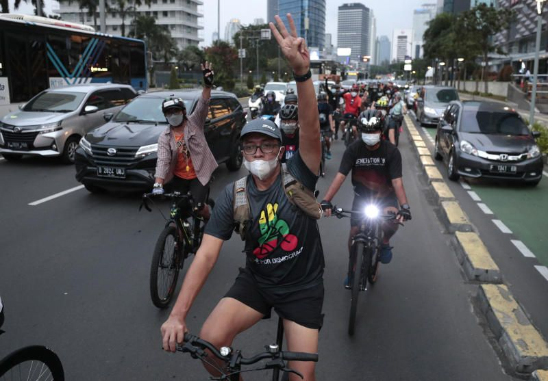 Activists flash a three-finger sign of defiance as they ride bicycles during a solidarity rally against the Myanmar military coup called