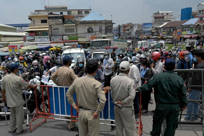 Police block motorists from passing a checkpoint due to lockdown restrictions introduced to try to halt a surge in cases of the Covid-19 coronavirus in Phnom Penh on Sunday, April 17, 2021. - AFP
